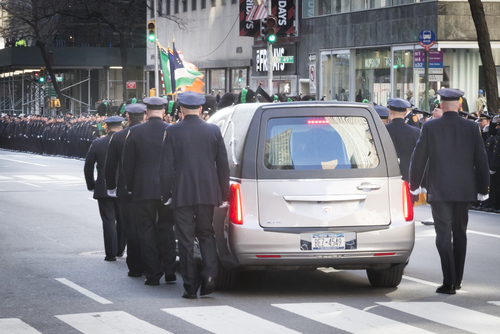 NEW YORK - JAN 13 2017: NYPD Det. Steven McDonald funeral procession and service at St Patricks Cathedral, 5th Avenue, Manhattan - Hearse and funeral procession motorcade leaves St Patricks Cathedral. (Shutterstock)