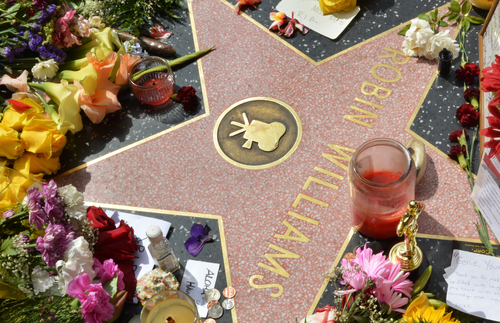 HOLLYWOOD, CA - AUGUST 12, 2014: Robin Williams' star on the Hollywood Walk of Fame is surrounded by flowers and various memorial tributes left by fans on August 12, 2014. (Shutterstock)