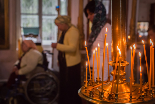 Russia. Ryazan region. Sreznevo. 07.12.2015 The church candles. The unidentified praying old woman in a wheelchair near the window, two women background in the Our Lady of Kazan Orthodox Cathedral. (Shutterstock)