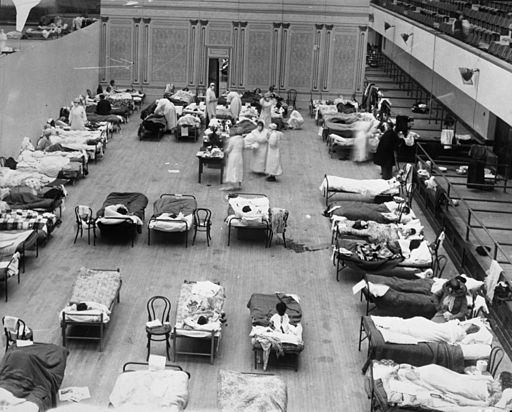 The photograph depicts volunteer nurses from the American Red Cross tending influenza sufferers in the Oakland Auditorium, Oakland, California, during the influenza pandemic of 1918. Oakland Public (Library/Wikimedia Commons)