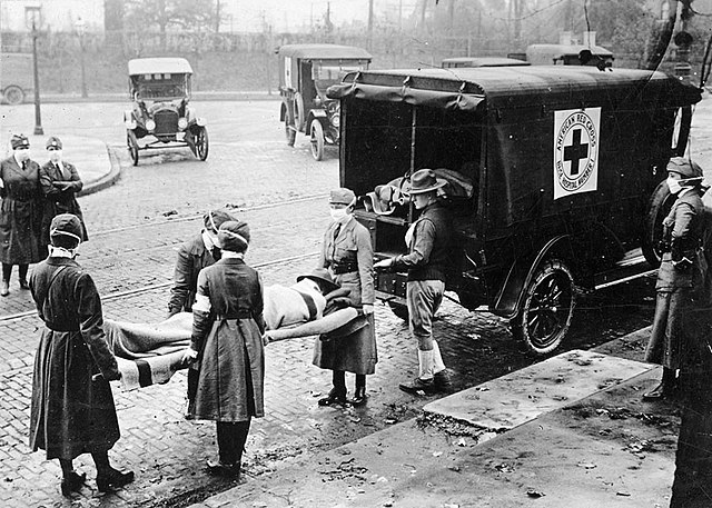 With masks over their faces, members of the American Red Cross remove a victim of the Spanish Flu from a house at Etzel and Page Avenues, St. Louis, Missouri. (Uncredited photographer for St. Louis Post Dispatch/Wikimedia Commons)